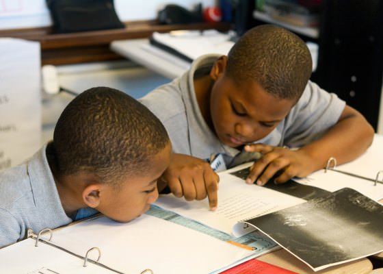 Two young male students work collaborate to read a text.