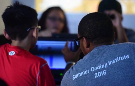 A Relay Summer Coding Institute participant works with a student during a pratice session at Relay.