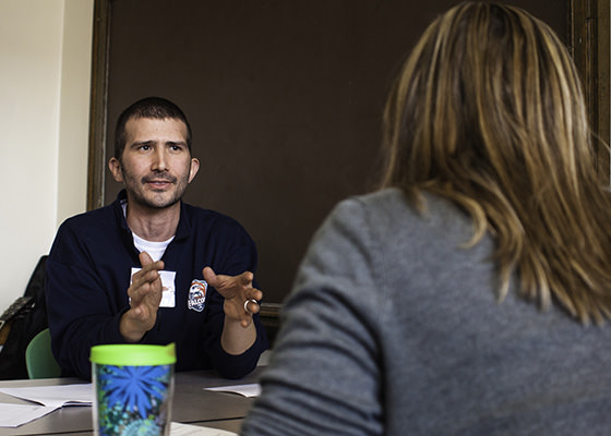 A male graduate student gestures toward a female colleague during a Relay Denver workshop.