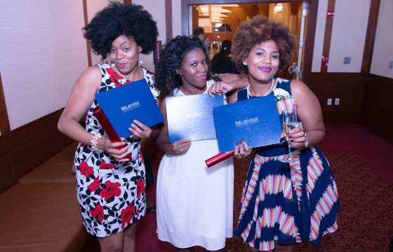 Three Relay New York graduates pose with their diplomas and batons at the 2015 graduation ceremony.