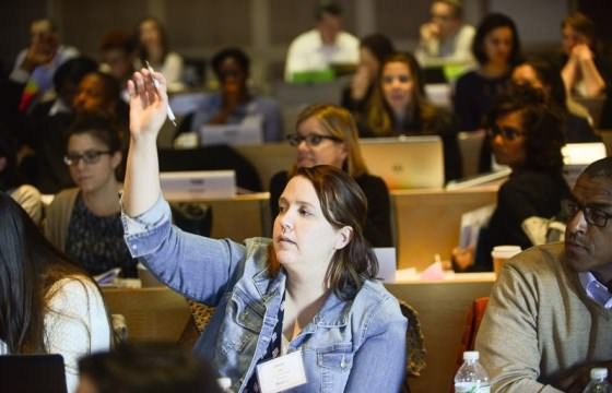 An NPAF leader raises her hand during a large class session.