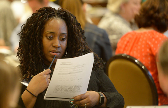Tanesia Simmons from KIPP St. Louis studies her papers as she works in the ballroom at the Sheraton in downtown Denver on June 19.