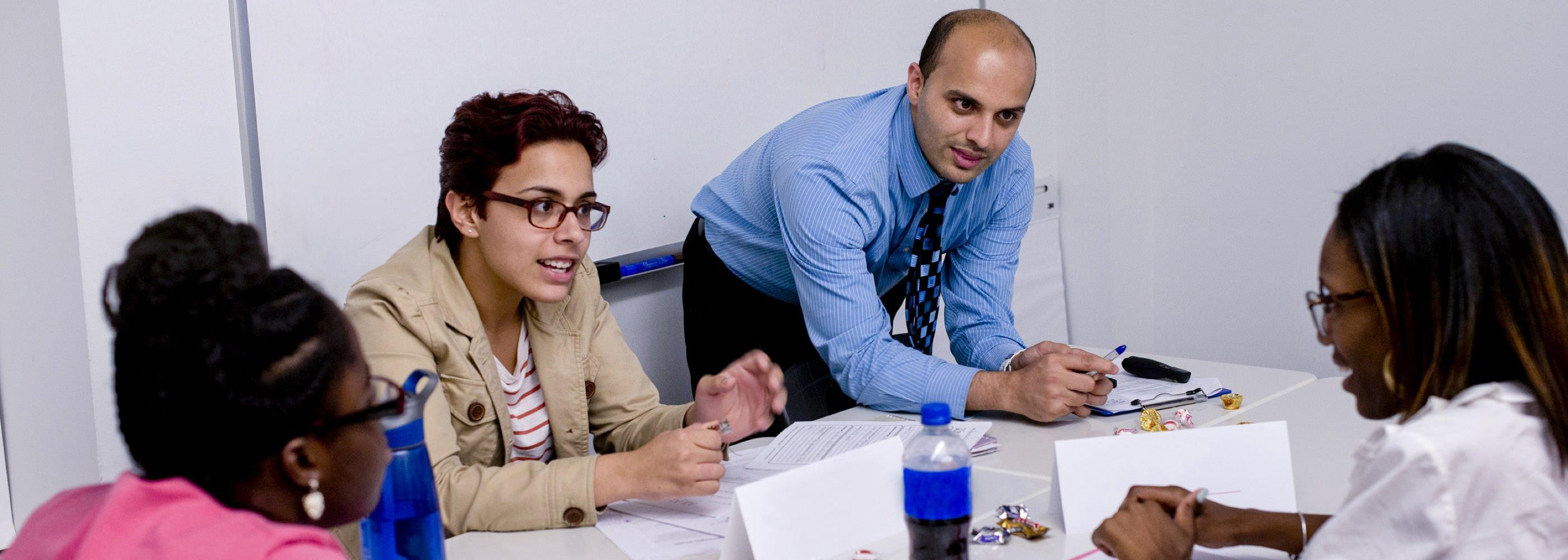 Relay New York Assistant Professor of Practice Jay Maqsood works with graduate students during a special education class.