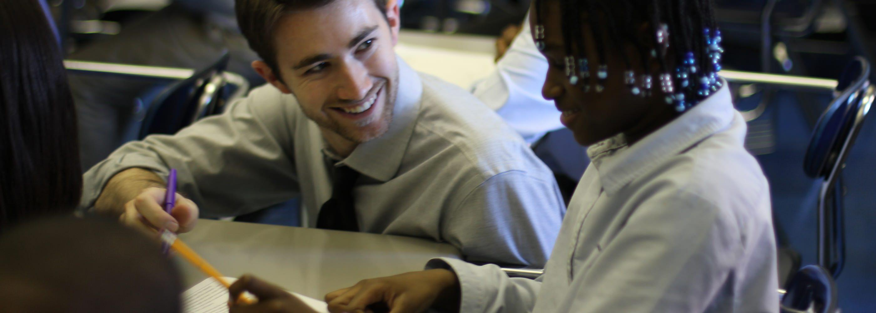 A male teacher works with a female student in Brooklyn, NY.
