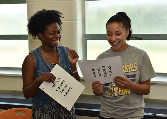 Two female graduate students laugh during a class session